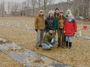 Volunteers, taking a break from planting back-cross chestnut seedlings in the Bok Orchard on a snowy day in April, 2013.