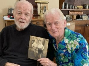 Jack and Jim side by side holding a photo of themselves as children